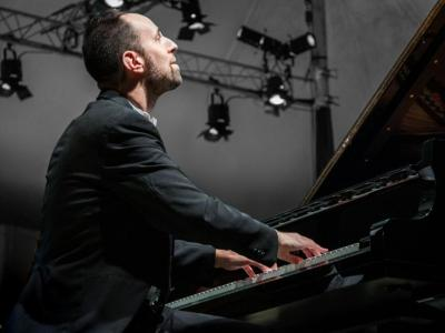View from the side at floor level: Spencer Myer looks up dreamily as he plays the piano. Stage lights are visible high in the air behind him.