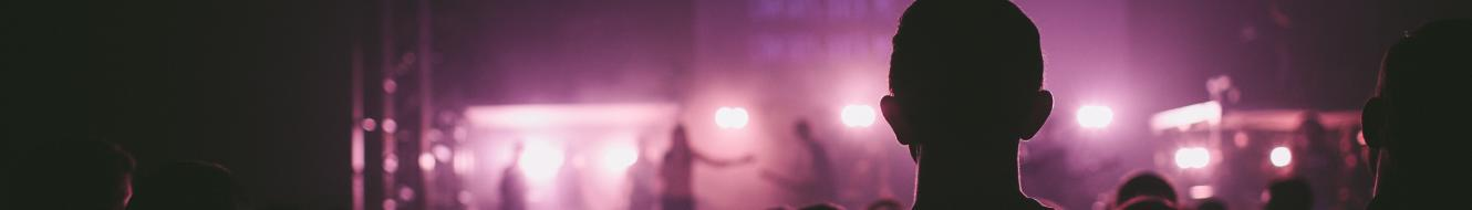 a person silhouetted by pink stage lights