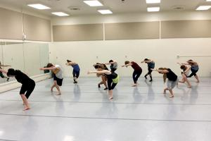 A group of students in a dance classroom doing a bowing pose with one arm and one leg crossed