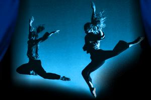 two leaping dancers in profile illuminated in blue light