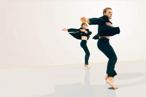 Two dancers in black clothing spin just above the floor