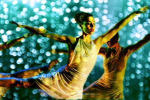Dancers perform under blue lights which look like rain