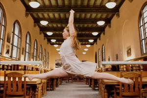 a dancer leaps between tables in an old fashioned library reading room