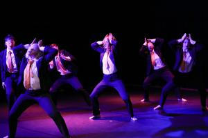 six performers wearing suits in saturated light. Some wear blindfolds