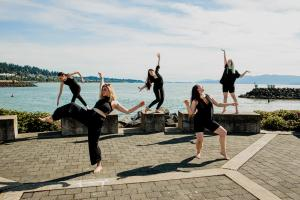 5 dancers, 3 on cement blocks and 2 on ground, in different artistic poses. A view of the bay behind them.