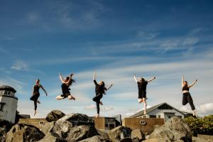 Five dancers leaping in the sky above a rocky terrain, each in a different artistic pose
