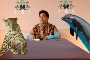 Chris Vargas sits at a dining table with a cheetah and a dolphin
