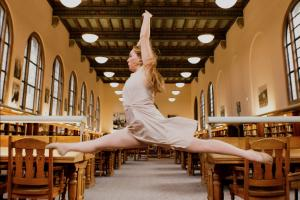 dancer leaping as between tables in an ornate library reading room