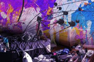 very messy room with intense splotches of color on the walls