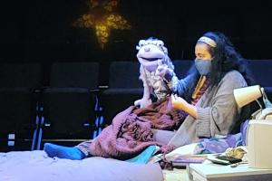 A person wearing a mask sits on a bed with a puppet. Behind them are empty theatre seats and a faintly lit star.