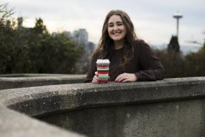 young person leaning on the curb of a fountain smiling holding a decorative paper coffee cup