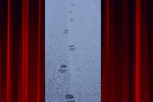 between theatre curtains appears fresh footprints on a snowy road