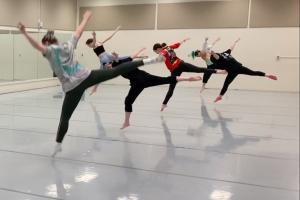 four dancers balance on one foot with back legs and arms extended