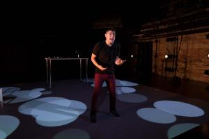 standing amid pools of light, Brian Quijada gestures energetically while speaking